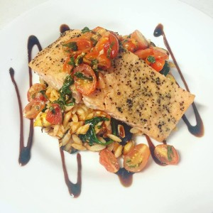 Salmon topped with Bruschetta and orzo pasta One World Theatre